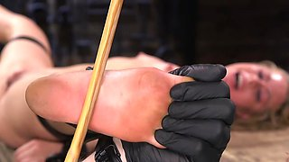 Attractive female has feet slapped by young man in black gloves