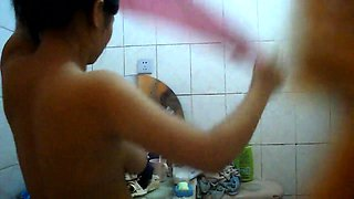 Voyeur spying on a busty mature Asian wife in the bathroom