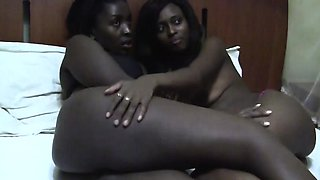 Horny African lesbians Nisa and Anaya relaxes on the bed.