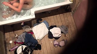 Voyeur spies on a beautiful young brunette in the bathtub