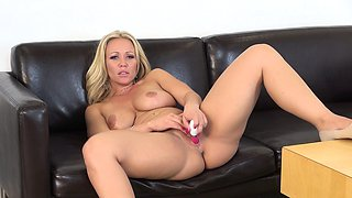 Buxom blonde milf Austin Taylor slides a dildo in and out of her twat