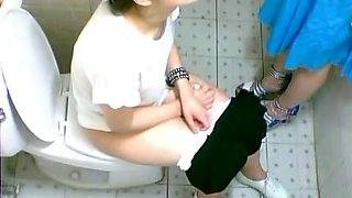 Two cute Asian girls spotted on a toilet cam pissing